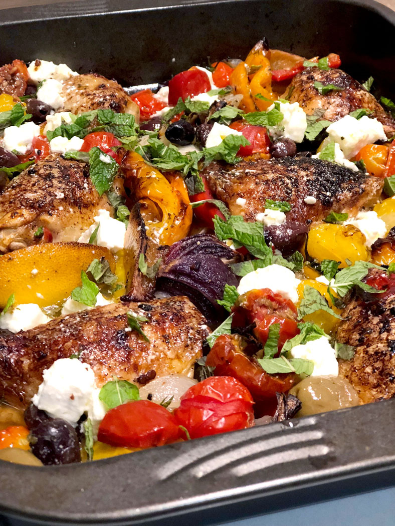 chicken with feta and tomato on a baking sheet